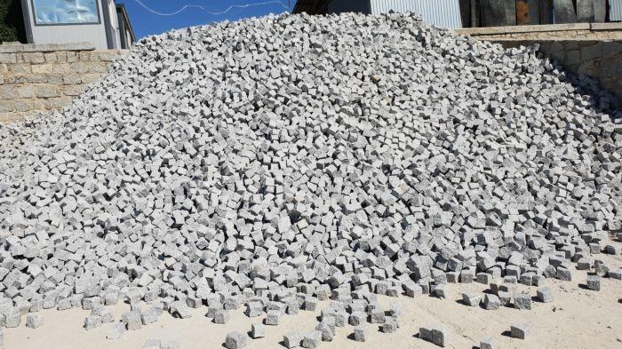 stos szarych kostek granitowych na piasku